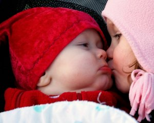 girl kissing baby red