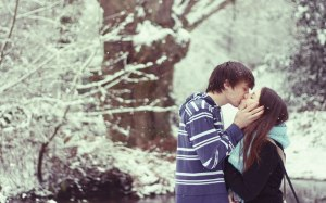 kissing while snowing under the trees