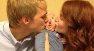 baby kissed by dad and mom between funny