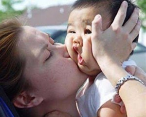 mother kisses baby big mouth