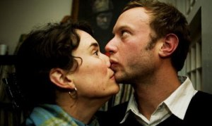woman kissing chin while man looking upside
